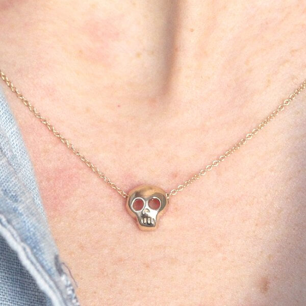 Simplified skull charm in gold