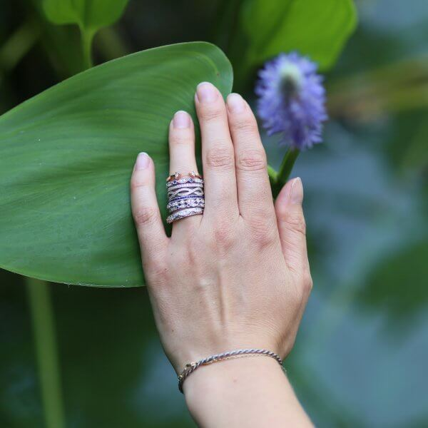 Stackable diamond and sapphire bands on a hand by OroSpot